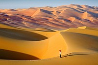 Woman in the sand dunes of the empty quarter desert. United Arab Emirates, UAE, Abu Dhabi, Liwa Oasis, Moreeb Hill, Tal Mireb. Model Released.