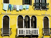 Washed clothes hanging on a yellow painted building. Cannaregio. Venice. Veneto. Italy.