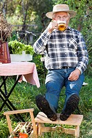 Thirsty man with glass of bear relaxing in the garden.