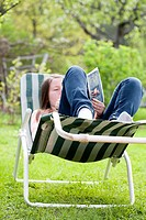 Teenage girl lying on a sun lounger and read a book outside in the garden.