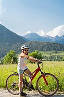 Portrait of a girl on a bike enjoying summer vacations in beautiful countryside, Bohinj Slovenia.