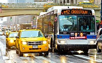 Mass Transit on Pershing Square, M42 MTA Crosstown Bus, outside Grand Central Terminal, morning rush hour during a snow and rain storm, Madison Avenue...