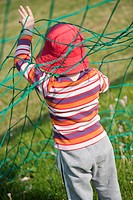 Young girl playing with net of football (soccer) goal.