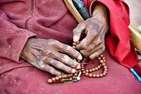 Tibetan pilgrim and prayer beads at the Boudhanath Stupa in Kathmandu, Nepal.