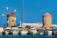 Windmills and tourists boats , in Mandraki harbor, Rhodes town , Rhodes island, Greece.