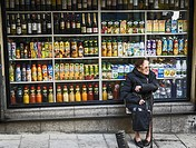 A old woman in a front store of drinks in a central street of Madrid, Spain.
