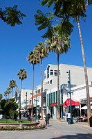 Pedestrians enjoy a sunny afternoon under the palm trees on Third Street Promenade, Santa Monica, City of Los Angeles, California, USA.