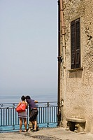 A couple enjoying the view from the terrace of Corso Vittorio Emmanuele, Tropea, Vibo Valentia, Calabria, Southern Italy, Italy.