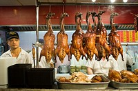 Peking Ducks on Display in Chinatown. Typical Asian food restaurant in Chinatown. Lacquered ducks hanging in the kitchen. Upon entering this district ...
