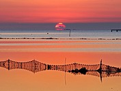 Sunrise at Alfacs Bay with fishing nets. Ebro River Delta Natural Park, Tarragona province, Catalonia, Spain.