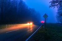 Dangerous road traffic situation in fog and rain. The cars are driving too fast on a wet slippery road on a rural road in Germany.