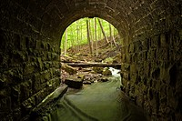 The entrance of a lovely stone block culvert looking out towards the forest in Tiffany Falls Conservation Area, Hamilton, Ontario, Canada.