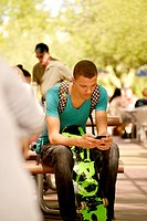 A young man texting on a college campus.