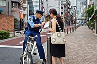 Policeman on bicycle helps pedestrian locate address in Roppongi, Tokyo, Japan.