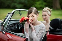 Bride with bouquet of roses in red convertable car.