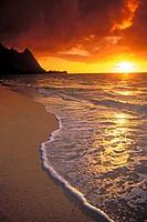 Sunset over surf, sand and peaks from Tunnels Beach, Ha´ena, Island of Kauai, Hawaii USA.