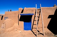 Ladder and adobe house with blue door, South House (World Heritage Site), Taos Pueblo, New Mexico USA.