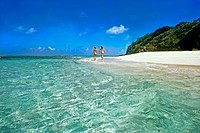 Two women walk naked on the white sand Caribbean beach in the Tobago Cays Marine Park, St. Vincent and the Grenadines