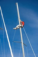 Benalmadena, Spain. Man repairing ships mast.