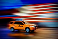 New York City Taxi whizzes along Times Square during the rain.
