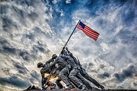 The Marine Corps War Memorial also called the Iwo Jima Memorial in Arlington, Virginia, with dramatic storm clouds in the background and a starburst a...