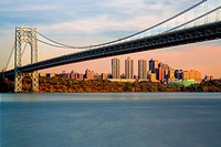 Wide view of the George Washington Bridge with the New York City skyline during Autumn. Jeffrey´s Hook Lighthouse also know as the Little Red Lighthou...