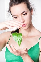 Woman looking amazed at green leaf floating in the air. Conceptual image of environment and the wonder of nature.