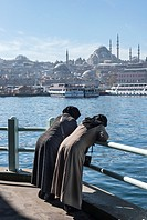 Two traditionaly dressed turkish women admire the view from the Galata bridge across the Golden Horn toward the Suleymaniye mosque and the Istanbul sk...