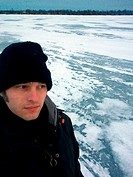 A man dressed in winter clothing taking a selfie on a frozen lake in the winter. Lake Simcoe, Ontario, Canada.