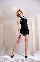 tall, young, attractive, dynamic and powerful woman in little black dress, in digitally manipulated room.
