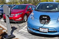 Electric cars plugged into an EV charging station in a workplace parking lot.