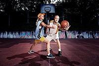 young basketball players on a street basketball court.