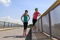 two women jogging over a bridge at the springtime.