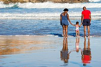 African couple holding the hands of their todddler daughter as they approach waves at the surfing beach, Victoria Bay, Garden Route, Western Cape, Sou...