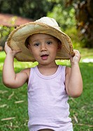 2 year old boy outdoors with cowboy hat.