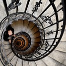 Asian woman in the spiral (helical) staircase in the tower of the Basilica of St Stephen. Hungary, Budapest, Pest, Belvaros. Model Released.