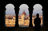 Silhouette of a woman watching the Hungarian Parliament Building from the Fisherman´s Bastion at sunset. Hungary, Budapest. Model Released.