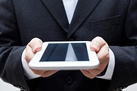 Detail of businessman holding digital tablet.