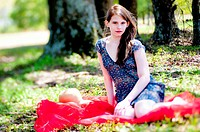 A 22 year old brunette woman wearing a summer dress sitting on a blanket in a pasture.