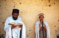 Orthodox christian man and woman during a mass. The man is reading the bible written in Ge´ez a forerunner of modern Amharic language. Bahir Dar, Ethi...