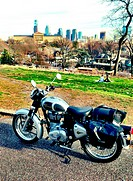 A motorcycle with the Philadelphia skyline in the background.