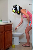 A woman wearing a helmet cleaning a toilet.