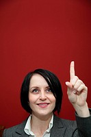 A black haired young woman pointing her finger up.