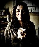 A woman enjoys a cup of coffee.