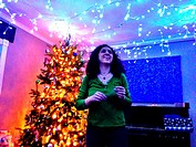 A woman decorates a room with holiday lights.
