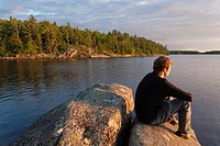 A man sitting on a rock as the sun sets over Georgian Bay. Massasauga Provincial Park, Ontario, Canada.