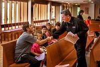 Catholic priest greets young Hispanic parishioners before mass at a Laguna Niguel, CA, Catholic church.
