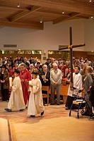The congregation watches as young robed altar servers carry candles as they lead a procession carrying a cross on Holy Thursday at St. Timothy´s Catho...
