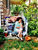 A woman takes a rest at a yard sale.