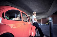urban portrait of a young woman with a classic car.